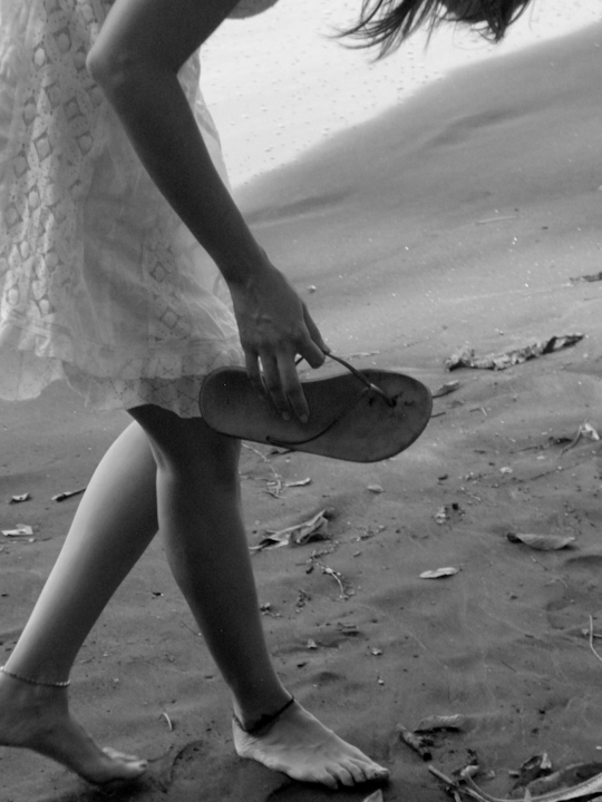 Woman with flip-flop on beach in b&w